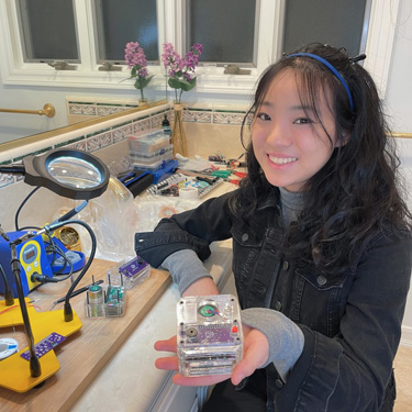 Vivien He with her earthquake early warning device in her makeshift soldering room converted from a bathroom